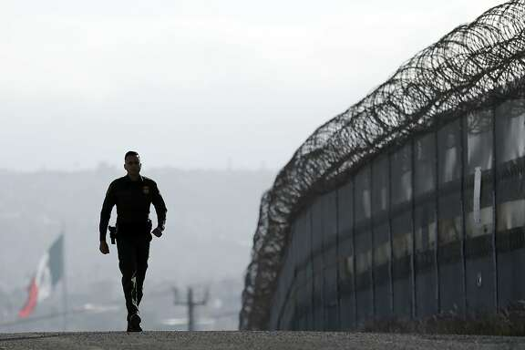 FILE - In this June 22, 2016 file photo, Border Patrol agent Eduardo Olmos walks near the secondary fence separating Tijuana, Mexico, background, and San Diego in San Diego. U.S. President Donald Trump will direct the Homeland Security Department to start building a wall at the Mexican border. (AP Photo/Gregory Bull, file)