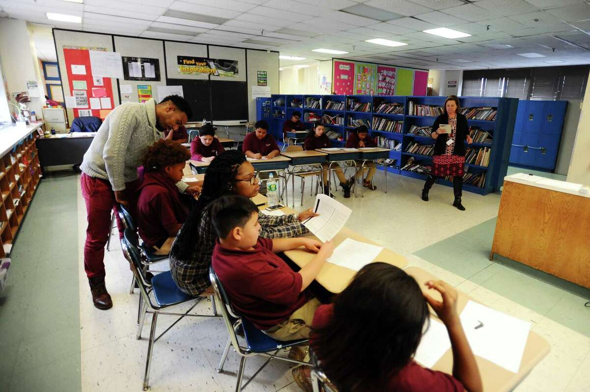 21-year-old peer professional Mechelle Lorthe, third from right, reads with 12-year-old Davidon Galdemz during a class inside Trailblazers Academy in Stamford, Conn. on Thursday, Jan. 19, 2017.