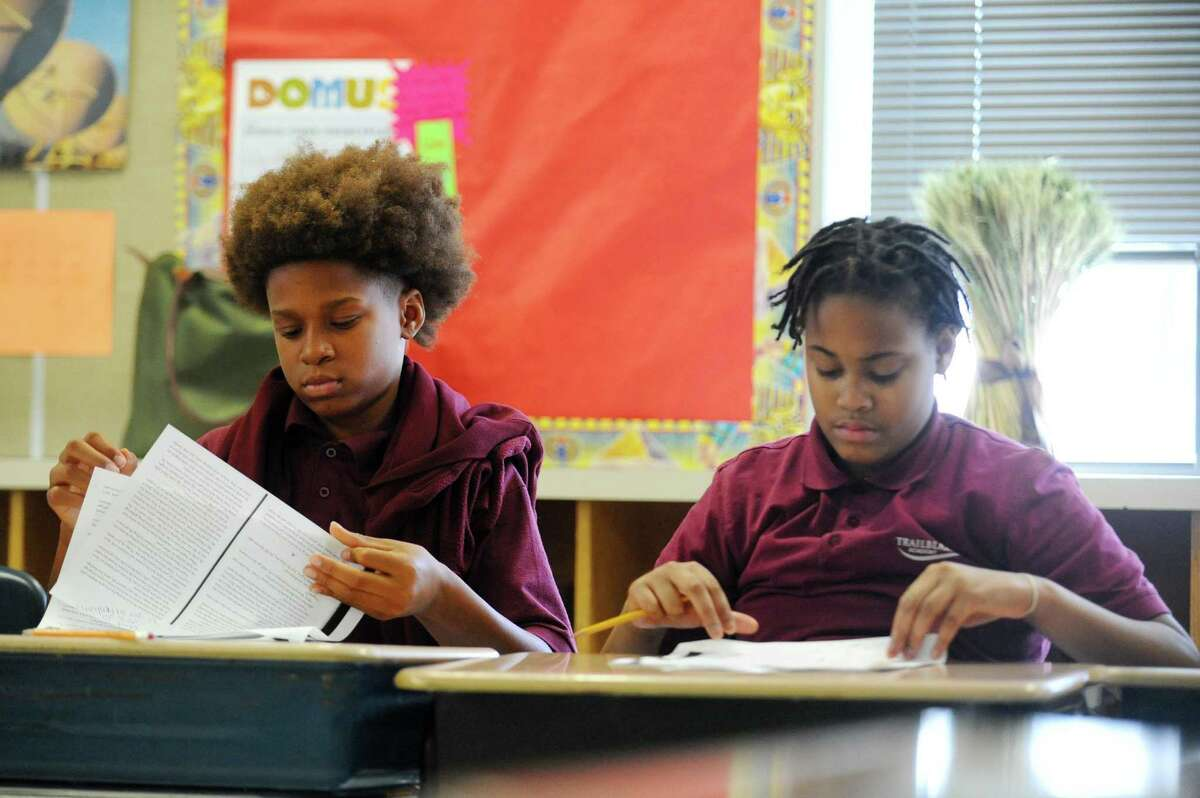 12-year-olds Devin Bates, left, and Janasia Jones turn the page while reading a chapter of a story inside Trailblazers Academy in Stamford, Conn. on Thursday, Jan. 19, 2017.