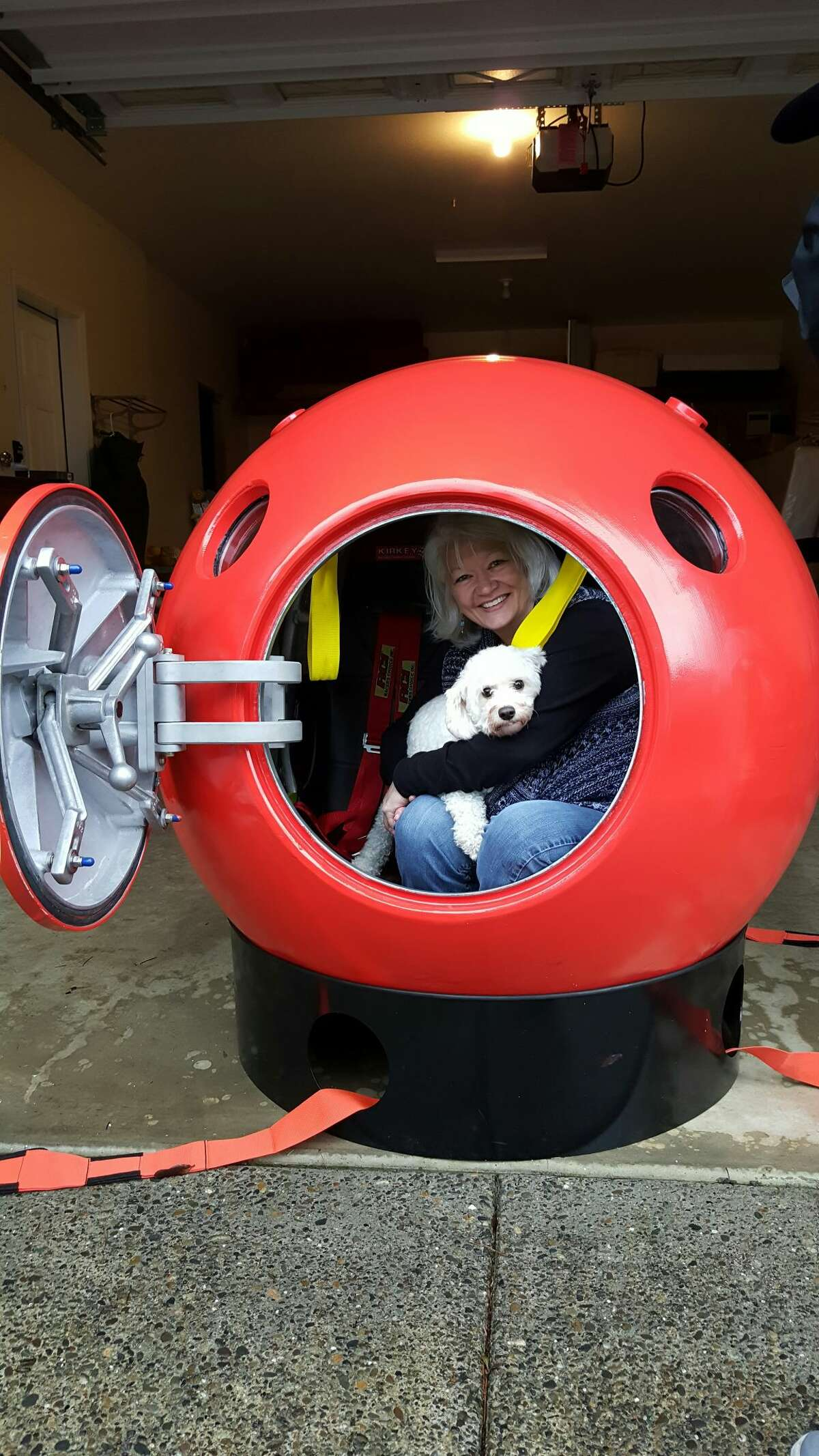 Jeanne Johnson and her dog sit inside her survival capsule.