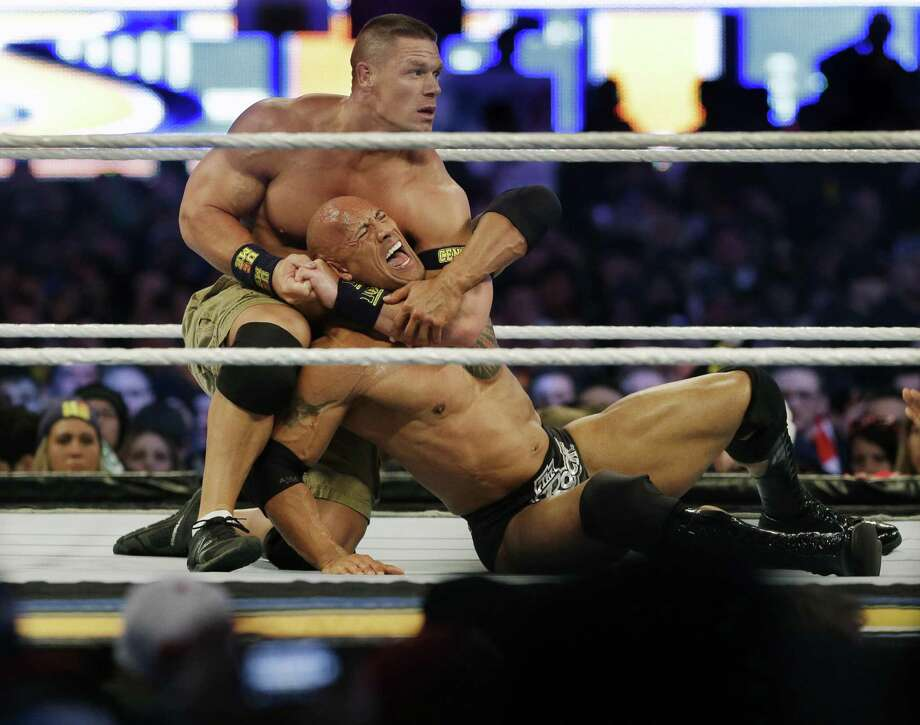 """Wrestler John Cena, top, chokes Dwayne Douglas Johnson, known as The Rock, as they wrestle during Wrestlemania in April. The Rock tops Forbes' latest highest-paid actors list with a $64.5 million year. Cena, the original WWE """"Face that Runs the Place"""" is now the main face of pro wrestling, with TV and film appearances that include hosting """"Saturday Night Live"""" and co-starring as Amy Schumer's gym-rat boyfriend in the comedy """"Trainwreck."""" Photo: Mel Evans /AP / AP"""
