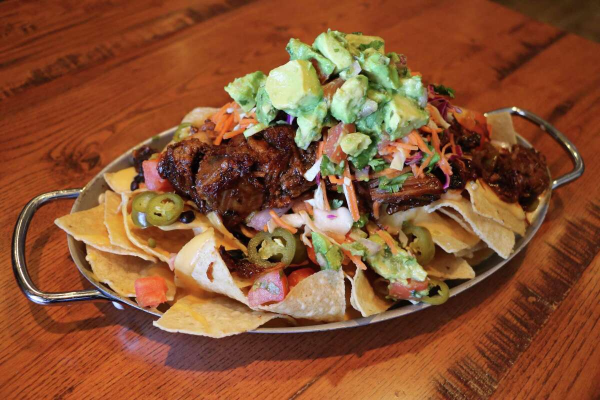 Chef Michael Collins at Asado Seafood & Grill makes a craveable version of nachos that includes a smoked cream sauce, smoked brisket, housemade black beans, pickled serranos, coleslaw pico de gallo and chunky guacamole.