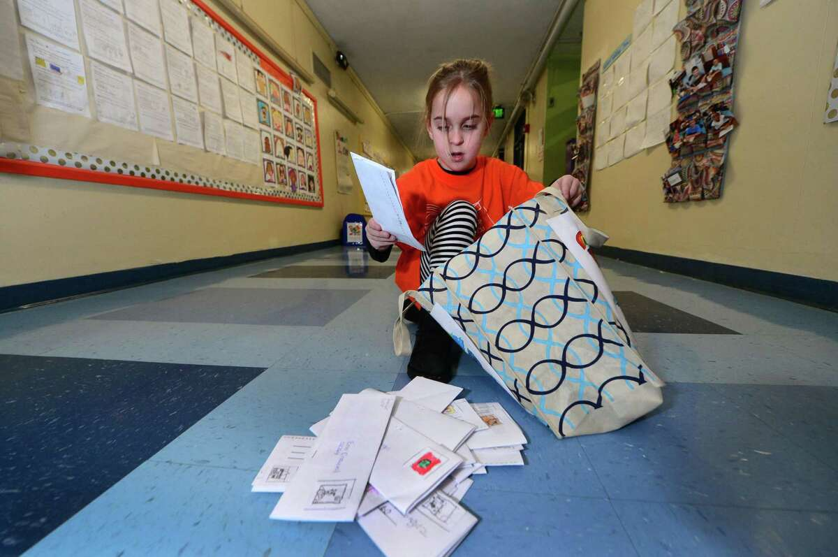 Columbus Magnet School second grader Gianna Testa sorts mail as her class recreates a working post office for the school Wednesday, January 25, 2017, in Norwalk, Conn. The second graders were assigned positions ranging from postal clerks to mail carriers. The annual program collected non-perishable food items for the Open Door Shelter in South Norwalk.