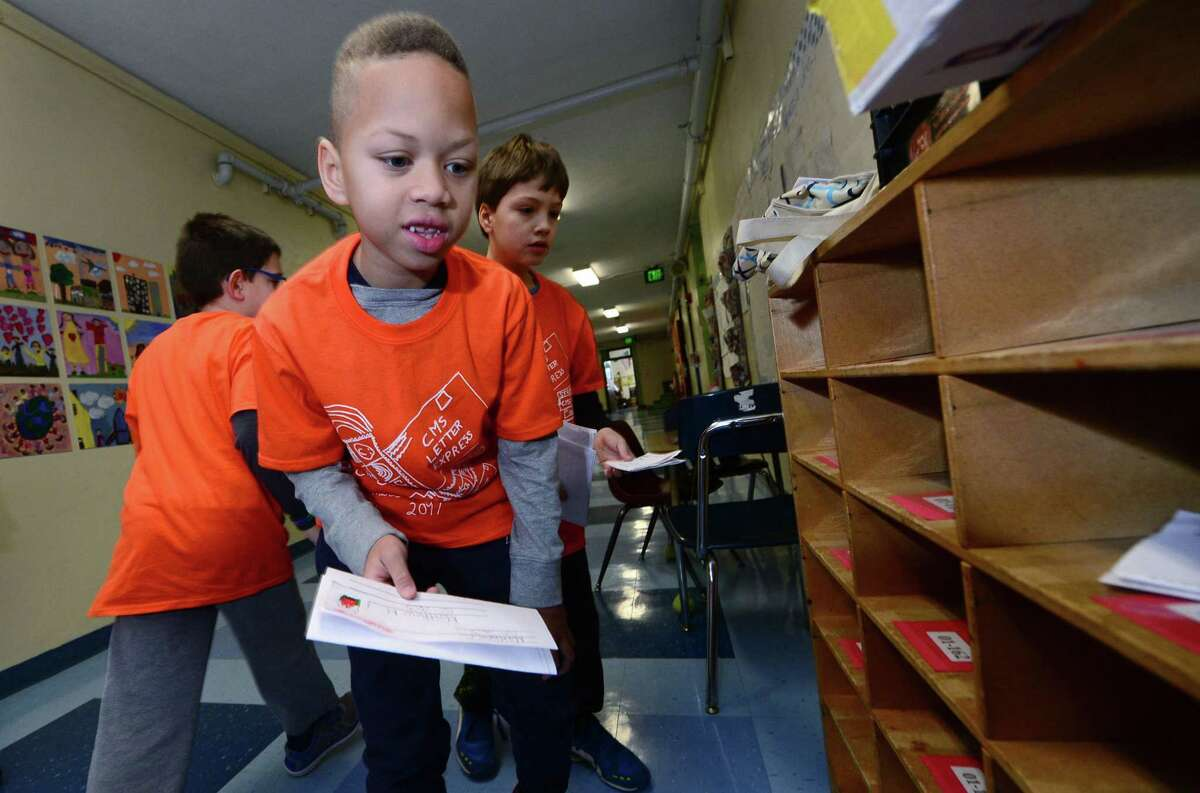 Columbus Magnet School second grader Joey Baski sorts mail as his class recreates a working post office for the school Wednesday, January 25, 2017, in Norwalk, Conn. The second graders were assigned positions ranging from postal clerks to mail carriers. The annual program collected non-perishable food items for the Open Door Shelter in South Norwalk.