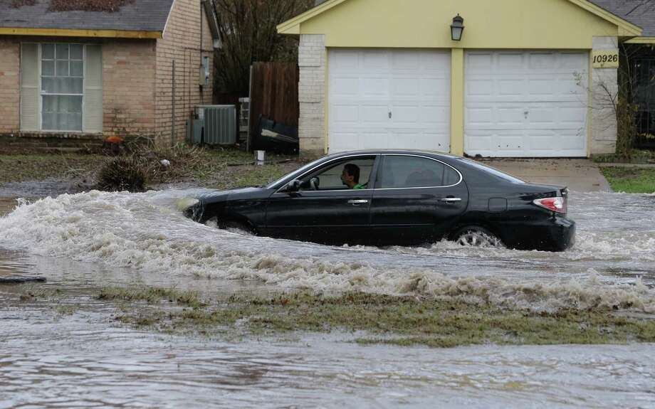 A man drives a car through the flooded street along West Bellfort at U.S. 59, Wednesday, Jan. 18, 2017.  ( Melissa Phillip/ Houston Chronicle) Photo: Melissa Phillip, Staff / Houston Chronicle 2017