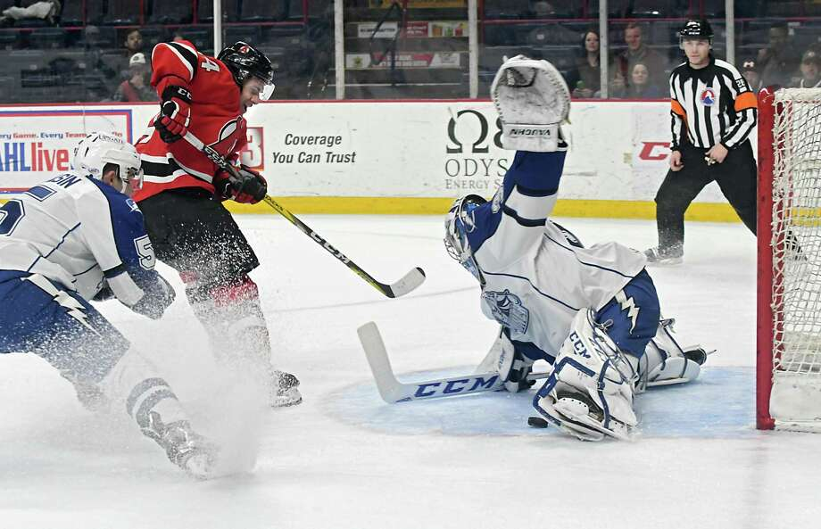 Albany Devils' Brian Gibbons, #14, takes a shot at the net but Syracuse Crunch goalie Adam Wilcox makes the save during a hockey game at the Times Union Center on Wednesday, Jan. 18, 2017 in Albany, N.Y. (Lori Van Buren / Times Union) Photo: Lori Van Buren / 20039347A