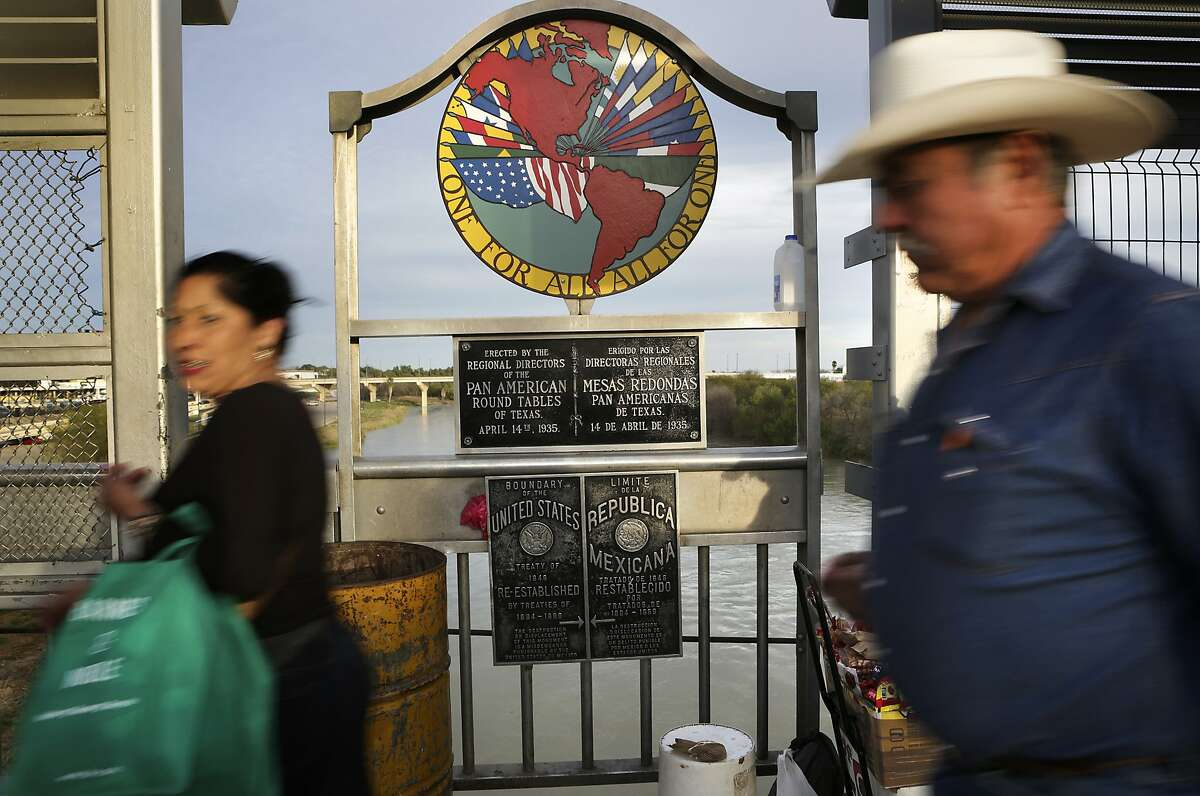 In this file photo, pedestrians cross the International Bridge #1 in Laredo, TX.