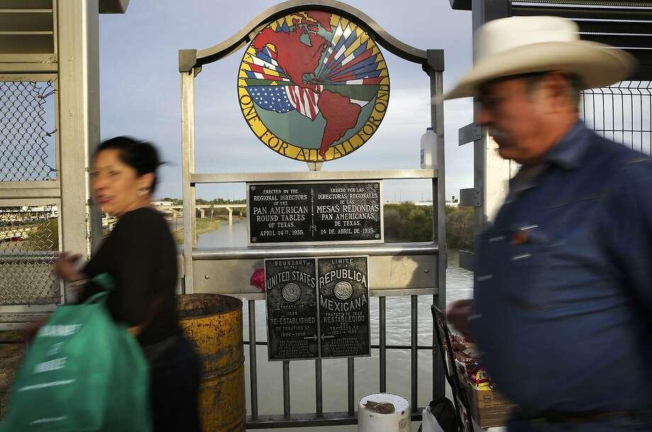 In this file photo, pedestrians cross the International Bridge #1 in Laredo, TX. Photo: Bob Owen, San Antonio Express-News