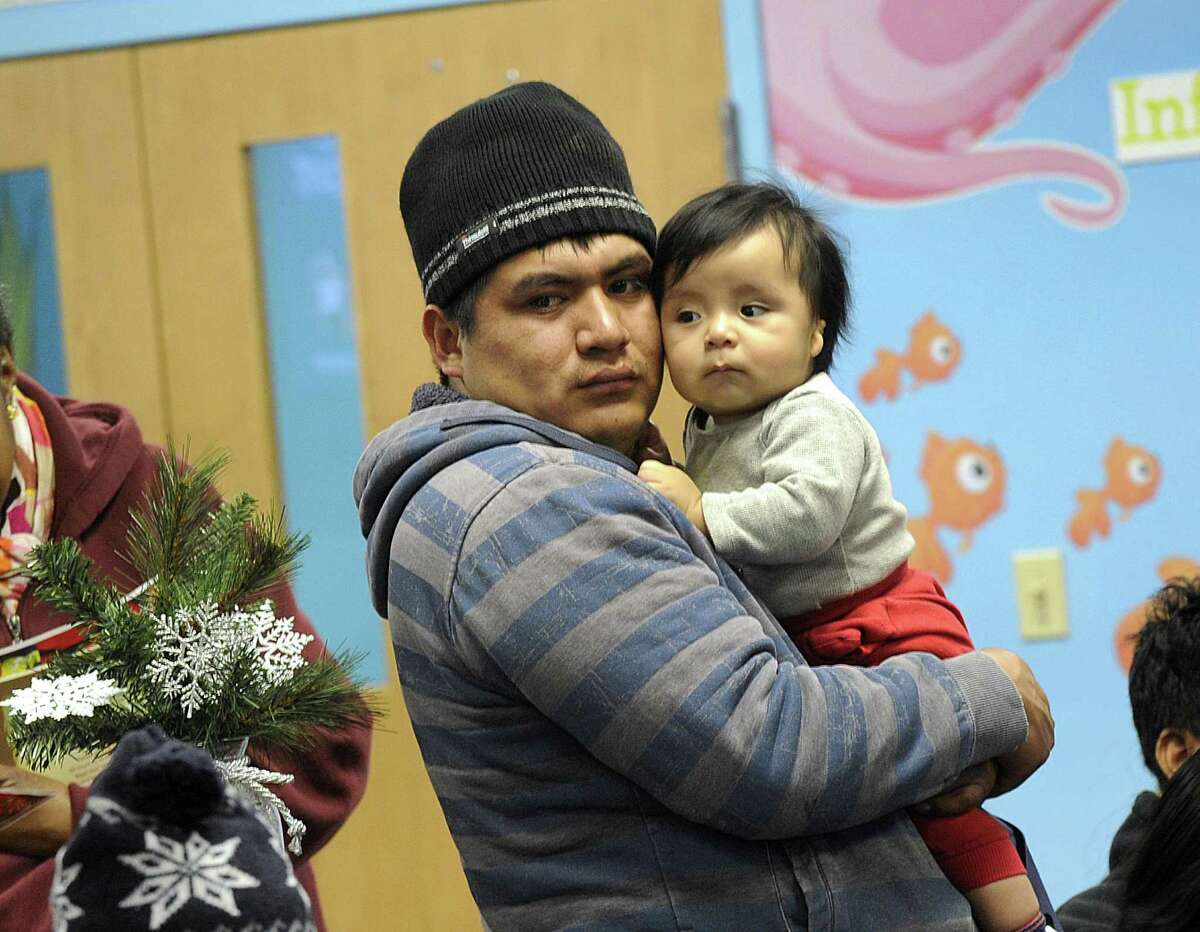 Edwin Magea, of Danbury, holds son, Dilan, 7 months, and waits for his turn at Wednesday's mobile food pantry at the Walnut Hill community Church in Bethel.
