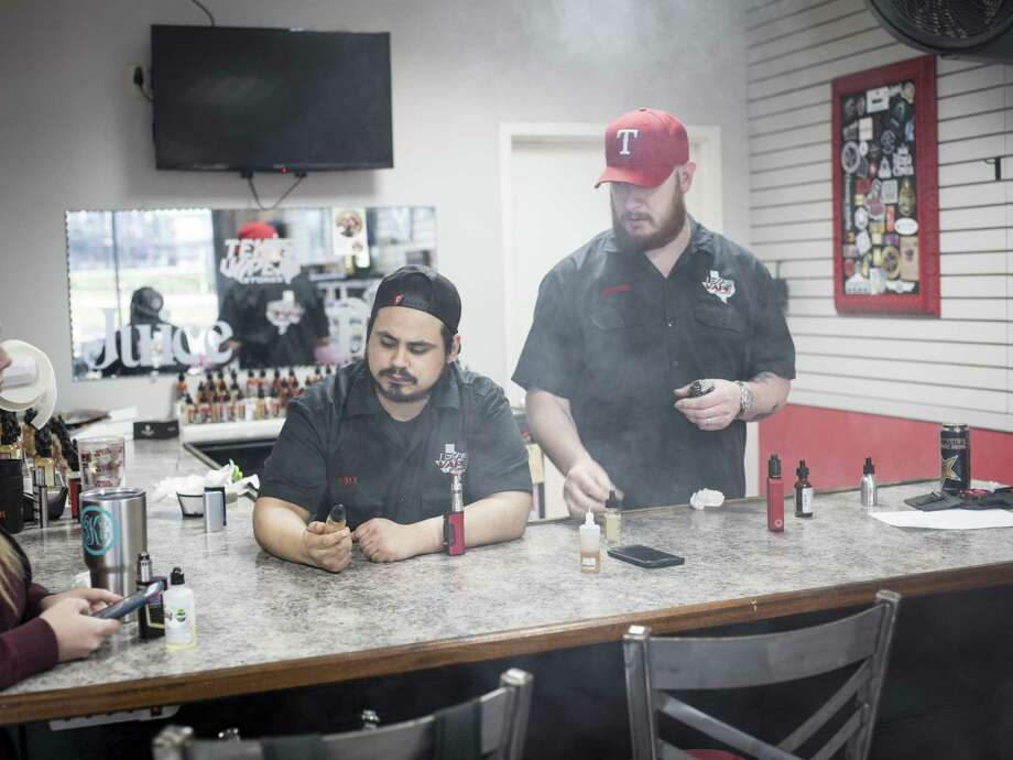 Employees Art Diaz, left, and Jimmie Allen, right, test a number of different e-juices at the Texas Vape Store off of Austin Highway on Jan. 23 in San Antonio. Photo: Matthew Busch /For The San Antonio Express-News / © Matthew Busch
