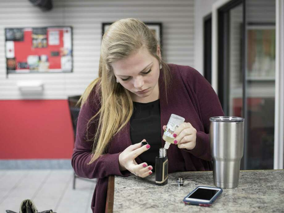 Shellbey Knight refills her e-cigarette with e-juice at the Texas Vape Store off of Austin Highway on Jan. 23 in San Antonio. On Jan. 11 San Antonio City Council approved a new law prohibiting merchants in the city limits from selling tobacco products to anyone under 21 years old. Photo: Matthew Busch /For The San Antonio Express-News / © Matthew Busch