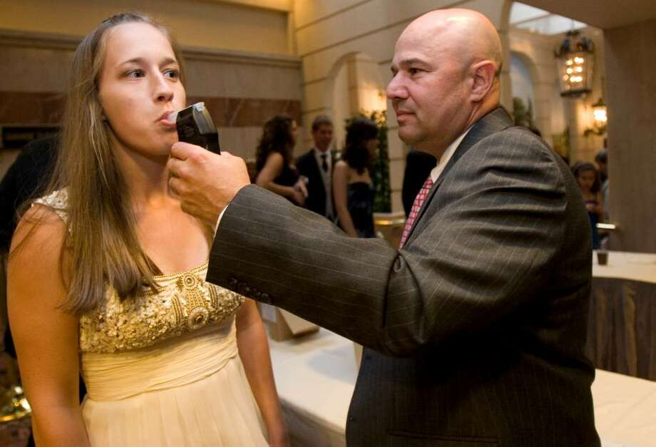 Betsy Hart has her breath tested for alcohol upon entering New Canaan's Senior Prom at the Stamford Marriot on Friday, May 21, 2010. Photo: Laura Buckman / Connecticut Post