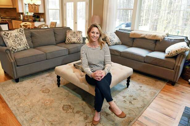 Jodi Emmons and her three-seat transitional couches, she loved them so much that she bought two, in her home Friday Nov. 18, 2016 in Wilton, NY.  (John Carl D'Annibale / Times Union)