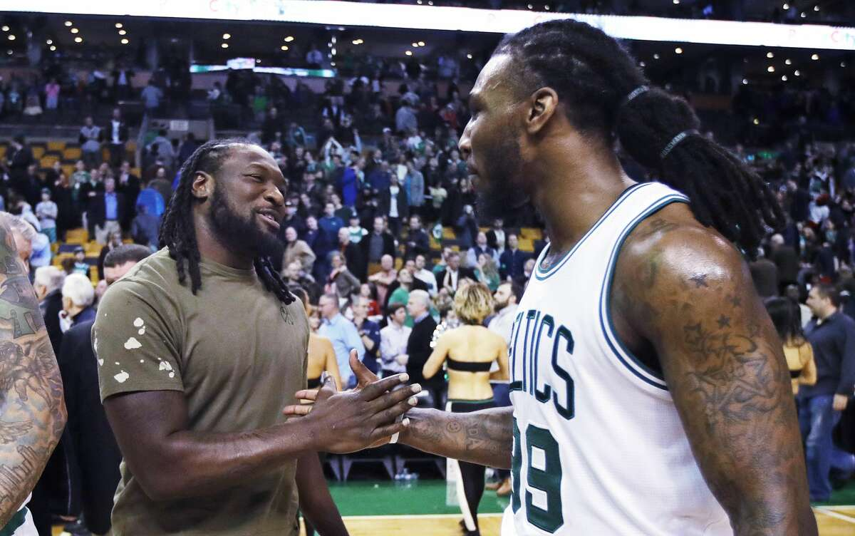 Boston Celtics forward Jae Crowder, right, shakes hands with New England Patriots running back LeGarrette Blount after an NBA basketball game against the Houston Rockets in Boston, Wednesday, Jan. 25, 2017. The Celtics defeated the Rockets 120-109. (AP Photo/Charles Krupa)