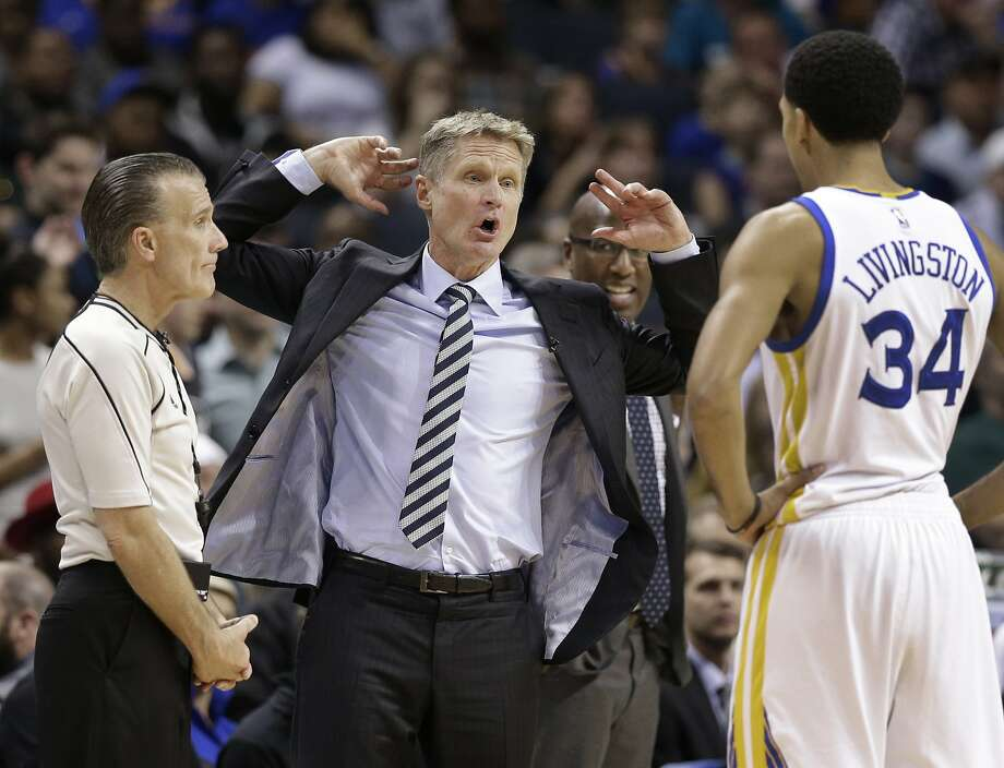 Golden State Warriors head coach Steve Kerr, center, with Shaun Livingston (34), argues a call with an official in the second half of an NBA basketball game against the Charlotte Hornets in Charlotte, N.C., Wednesday, Jan. 25, 2017. The Warriors won 113-103. (AP Photo/Chuck Burton) Photo: Chuck Burton, Associated Press
