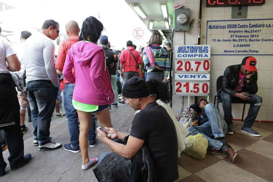 Cubans talk with relatives and watch the news on cellphones as a group of of 250 Cubans wait for news at the international bridge in Nuevo Laredo on Wednesday. Photo: Bob Owen / San Antonio Express-News / San Antonio Express-News