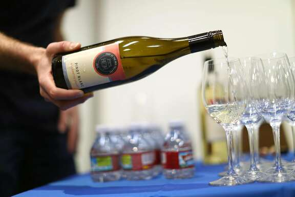 Foot of the Bed Cellars' Martin Sheehan-Stross pours  a glass of pinot blanc during wine club pick up party in San Francisco, Calif., on Wednesday, January 25, 2017.
