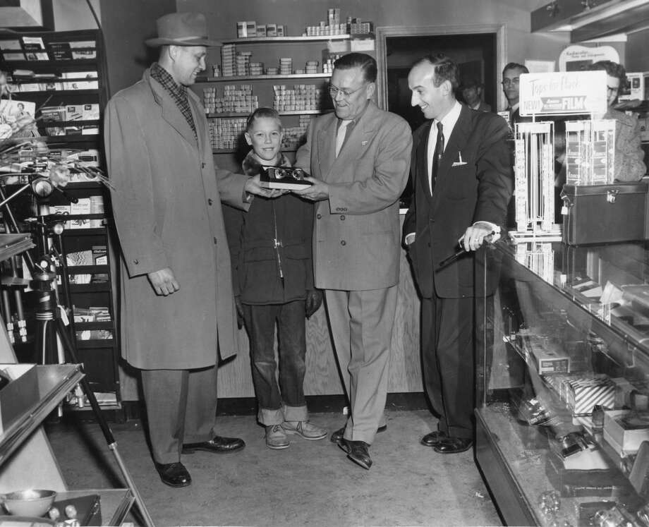 D.D. McCollister, left, is the winner of the grand prize, which Wright's Studio and Camera Shop awarded in connection with its 25th anniversary. McCollister is shown receiving a stereo camera. Also pictured, from left, McCollister's son Roger; Chester J. Wright, co-owner, and William Meier, retail manager of Wright's. November 1955 Photo: Daily News File Photo