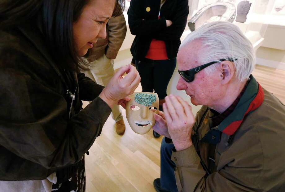Docent Gabby Gamez (left) attempts to describe the different materials on a mask as Larry Johnson gets a feel for the textures during a guided tour for the visually impaired throughout the San Antonio Museum of Art in 2016. Many readers love Johnson's inspiring commentaries and spirit of adventure. Photo: Kin Man Hui /San Antonio Express-News / ©2016 San Antonio Express-News