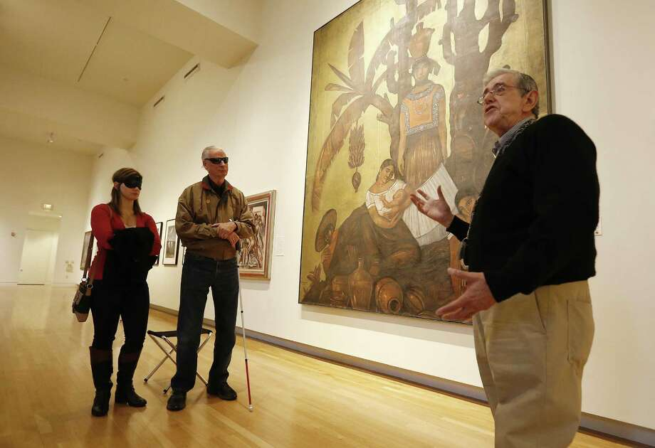 Docent Gustavo Valadez (right) describes a painting by artist Roberto Montenegro as visually-impaired patron Larry Johnson (second from left) and his volunteer guide Megan Gerlach listen during a guided tour of artwork at the San Antonio Museum of Art earlier this month. Several docents guided visually-impaired patrons like Johnson on a tour in the museum's artwork from the Americas. Once a month, the museum offers guided tours where docents use tactile samples, music and descriptive narrations to fill the void of vision for their guests to appreciate the artwork on display. Gerlach was offered to wear a mask to help her appreciate the descriptive nature of the tour. Photo: Kin Man Hui /San Antonio Express-News / ©2016 San Antonio Express-News