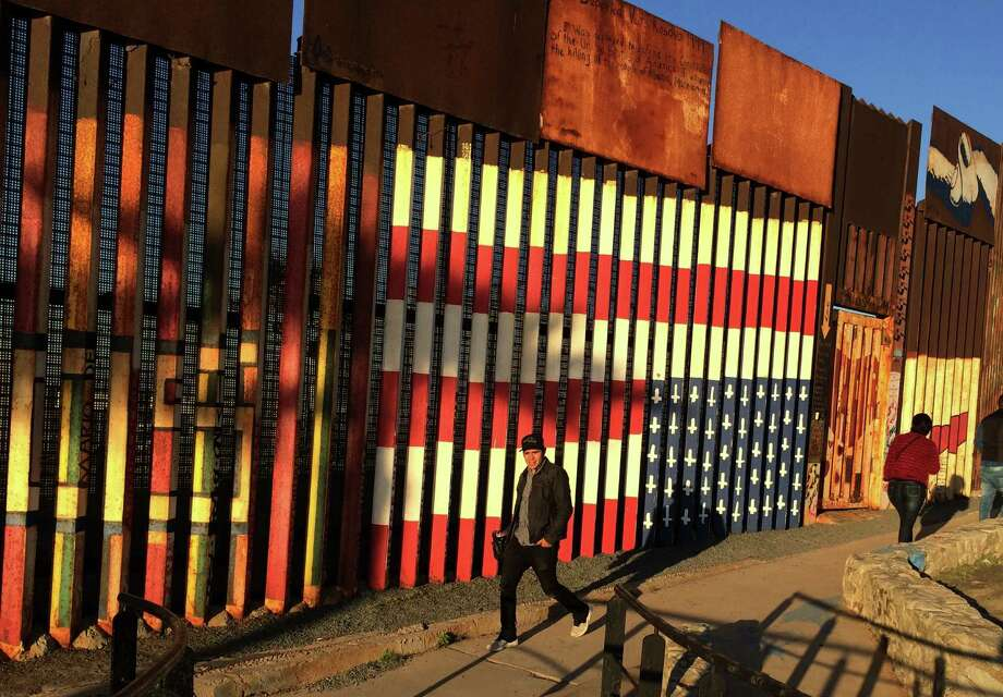 """People pass graffiti along the border structure in Tijuana, Mexico, Wednesday, Jan. 25, 2017. President Donald Trump moved aggressively to tighten the nation's immigration controls Wednesday, signing executive actions to jumpstart construction of his promised U.S.-Mexico border wall and cut federal grants for immigrant-protecting """"sanctuary cities.""""Click ahead to see what the U.S.-Mexican border really looks like. Photo: Julie Watson, Associated Press / Copyright 2017 The Associated Press. All rights reserved."""
