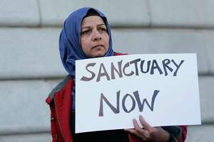 """Moina Shaiq holds a sign at a rally outside of City Hall in San Francisco, Wednesday, Jan. 25, 2017. President Donald Trump moved aggressively to tighten the nation's immigration controls Wednesday, signing executive actions to jumpstart construction of his promised U.S.-Mexico border wall and cut federal grants for immigrant-protecting """"sanctuary cities."""" (AP Photo/Jeff Chiu)"""