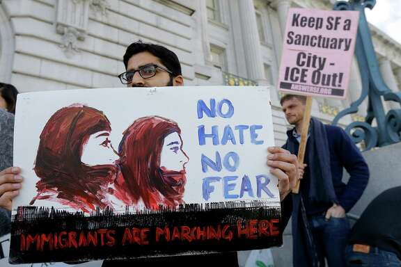 "Anirvan Chatterjee, left, of the Alliance of South Asians Taking Action, holds a sign at a rally outside of City Hall in San Francisco, Wednesday, Jan. 25, 2017. President Donald Trump moved aggressively to tighten the nation's immigration controls Wednesday, signing executive actions to jumpstart construction of his promised U.S.-Mexico border wall and cut federal grants for immigrant-protecting ""sanctuary cities."" (AP Photo/Jeff Chiu)"