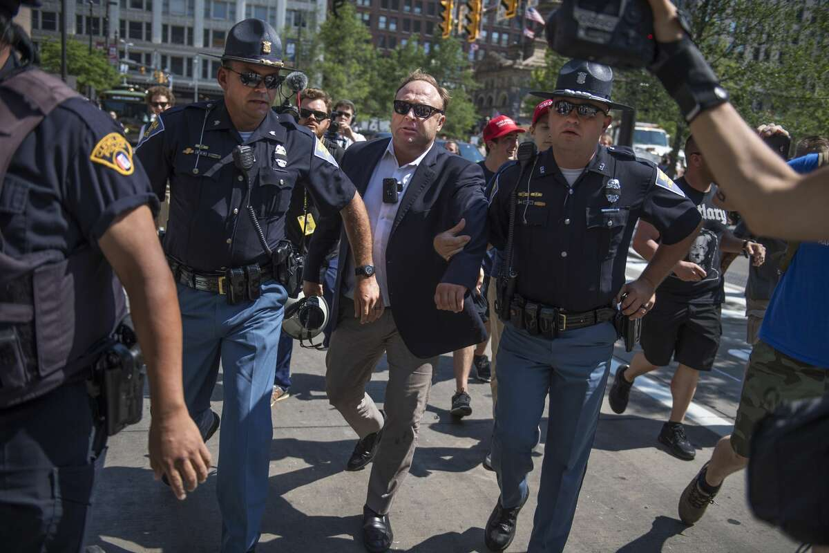 FILE - Radio host Alex Jones is escorted from a rally in the Public Square after inciting a confrontation near the Republican National Convention at the Quicken Loans Arena in Cleveland.