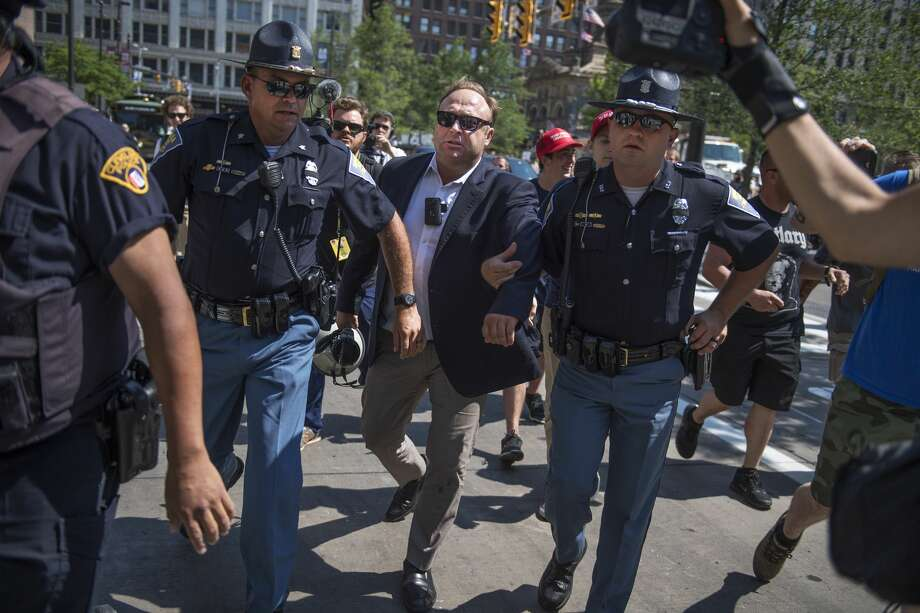 FILE — Radio host Alex Jones is escorted from a rally in the Public Square after inciting a confrontation near the Republican National Convention at the Quicken Loans Arena in Cleveland. Photo: Tom Williams/CQ-Roll Call, Inc.