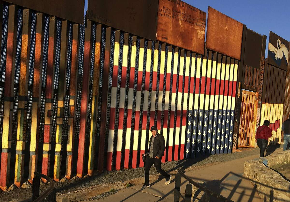 """People pass graffiti along the border structure in Tijuana, Mexico, Wednesday, Jan. 25, 2017. President Donald Trump moved aggressively to tighten the nation's immigration controls Wednesday, signing executive actions to jumpstart construction of his promised U.S.-Mexico border wall and cut federal grants for immigrant-protecting """"sanctuary cities."""" (AP Photo/Julie Watson)"""