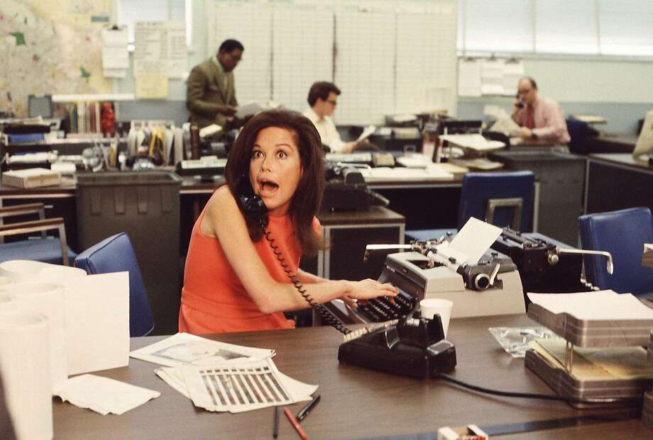 American actress Mary Tyler Moore mouths surprise on the telephone while simultaneously typing as others work in the background in a scene from 'The Mary Tyler Moore Show' (also known as 'Mary Tyler Moore'), Los Angeles, California, early 1970s. Moore wears a sleeveless orange dress as she sits behind her desk. (Photo by CBS Photo Archive/Getty Images) Photo: Getty Images, CBS Photo Archive