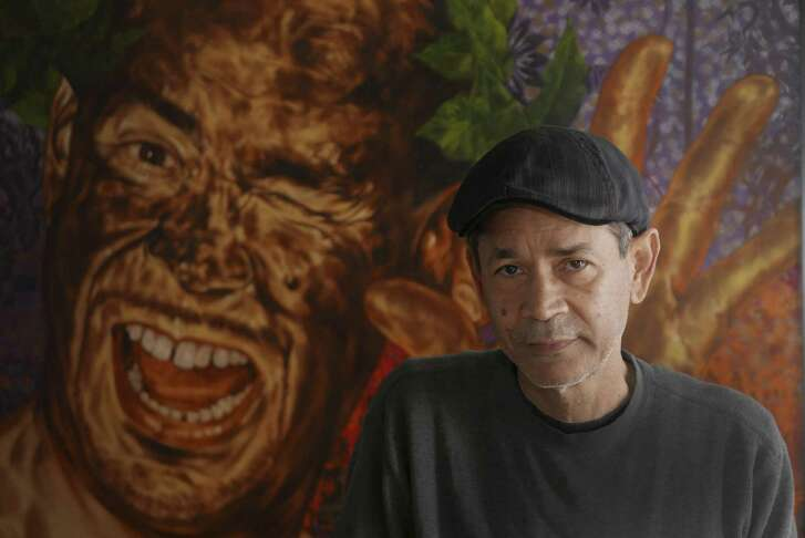 "Artist Angel Rodriguez-Diaz at home in San Antonio. The artist, known for his self-portraits, stands before a work titled ""The Good Old Days."""