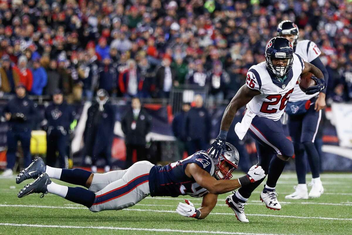 Houston Texans running back Lamar Miller (26) runs past a dive by New England Patriots defensive end Trey Flowers (98) during the first quarter of an NFL divisional playoff game at Gillette Stadium, Saturday, January 14, 2017. ( Karen Warren / Houston Chronicle )
