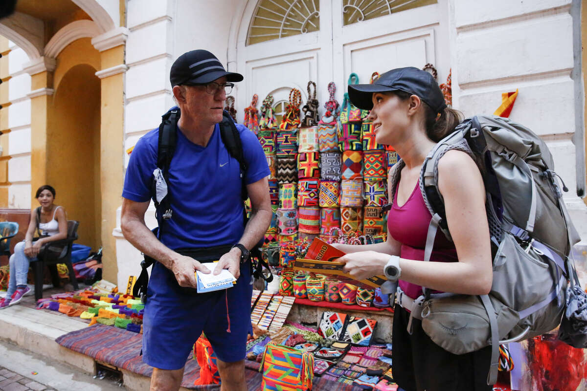 """Scott (left) and Blair (right) must find two matches to the sample mochilas they are given then return them to a street vendor in order to receive the next clue on an """"The Amazing Race"""" episode in 2015."""