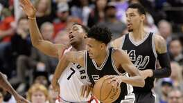 Spurs' Dejounte Murray is called for an offensive foul on the Raptors' Kyle Lowry.