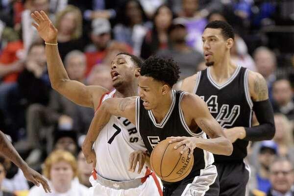 San Antonio Spurs guard Dejounte Murray (5) fouls Toronto Raptors guard Kyle Lowry (7) during the second half of an NBA basketball game Tuesday, Jan. 24, 2017, in Toronto. (Frank Gunn/The Canadian Press via AP)