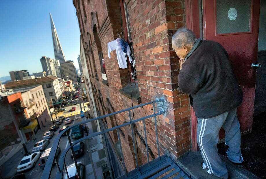 Jiu Yin Tong, 79, looks out from a 3rd floor fire escape at his SRO at 937 Clay Street on Thursday, Jan. 26, 2017 in San Francisco, Calif.   Chinatown Community Development Center is alleging that the owner of a Chinatown CDC (SRO) is harassing long-time residents -- hoping to get them to leave in order to replace them with high rent paying tech workers and students. Photo: Paul Kuroda, Special To The Chronicle