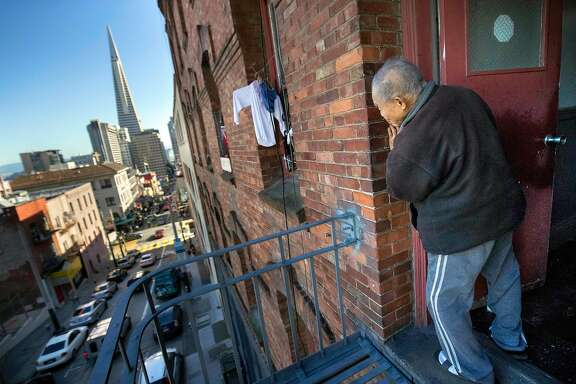 Jiu Yin Tong, 79, looks out from a 3rd floor fire escape at his SRO at 937 Clay Street on Thursday, Jan. 26, 2017 in San Francisco, Calif.   Chinatown Community Development Center is alleging that the owner of a Chinatown CDC (SRO) is harassing long-time residents -- hoping to get them to leave in order to replace them with high rent paying tech workers and students.