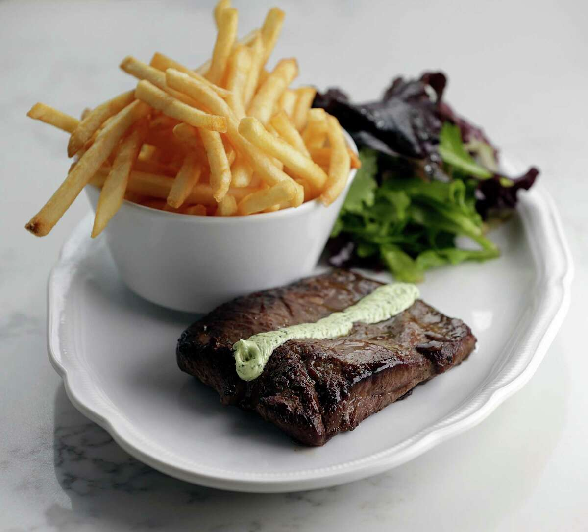 The Steak Frites (8 oz. flat iron) with pommes frites, with spring mix salad at Brasserie du Parc, at One Park Place in downtown Houston.