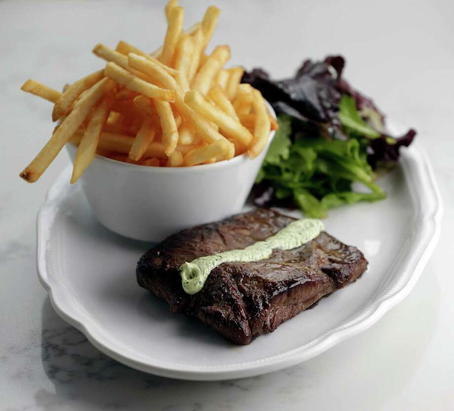 The Steak Frites (8 oz. flat iron) with pommes frites, with spring mix salad at Brasserie du Parc, at One Park Place in downtown Houston. Photo: James Nielsen, Houston Chronicle / © 2017  Houston Chronicle
