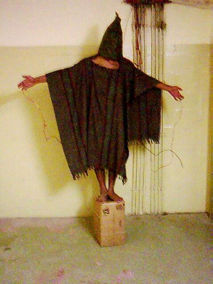 ** HOLD FOR RELEASE UNTIL 12:01 a.m. EDT, WEDNESDAY, JUNE 18, 2008 ** ** FILE ** This is a file image obtained by The Associated Press which shows an unidentified detainee standing on a box with a bag on his head and wires attached to him in late 2003 at the Abu Ghraib prison in Baghdad, Iraq. Years after being released by the U.S. military, former detainees held in Abu Ghraib and Guantanamo Bay Naval Base are suffering debilitating injuries and mental disorders from their interrogation and alleged torture, according to a new report by a human rights group. (AP Photo) Photo: AP
