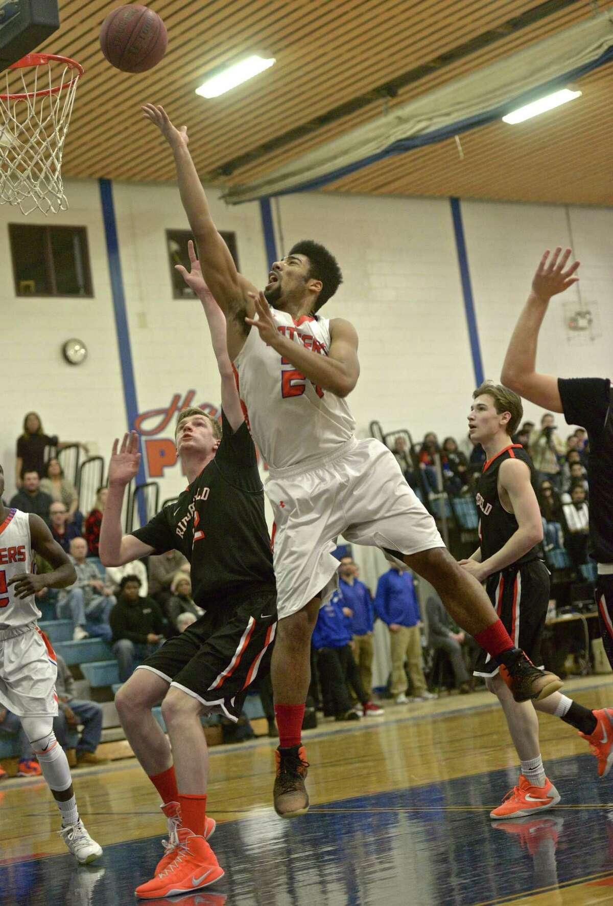 Danbury's Marcus Fox (24) goes to the basket over Ridgefield's Nicholas Laudati (42) in the boys high school basketball game between Ridgefield and Danbury high schools, Tuesday night, January 10, 2017, at Danbury High School, Danbury, Conn.