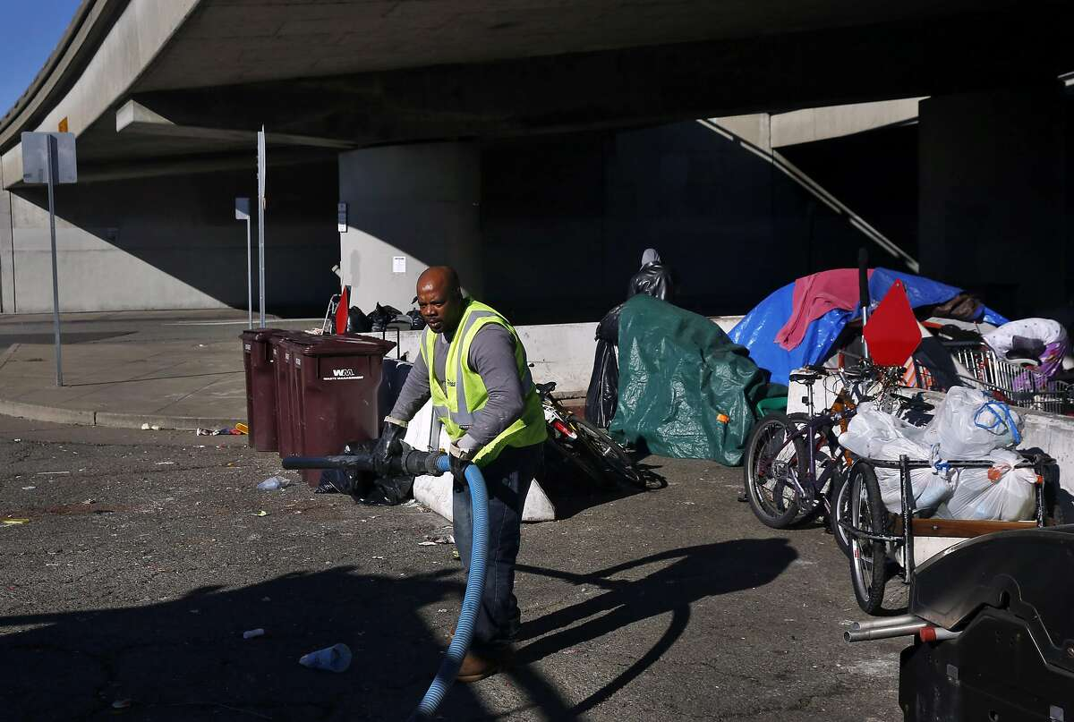 Bobby Stanfield, a contractor for the city, finishes up cleaning two port-o-potties at a sanctioned homeless camp underneath Interstate 580 on Peralta Street Jan. 13, 2017 in Oakland, Calif.