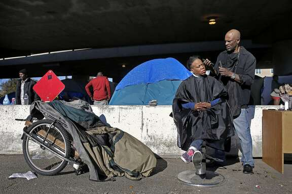 "Latasha Hardman gets a haircut from her boyfriend Eugene Rumbley at Oakland's first sanctioned encampment, the ""Compassionate Community"" experiment, where they have been living for the past three months, under the 580 freeway at 35th and Magnolia streets in Oakland, Ca., on Thursday Jan. 26, 2017."