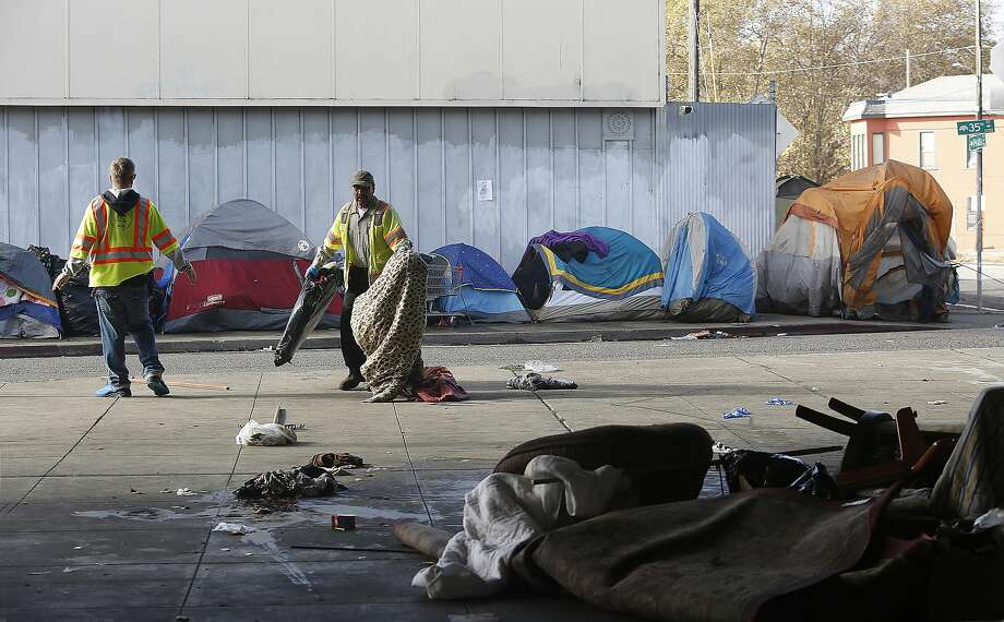 City workers clean up at the homeless encampment on 35th and Magnolia streets in Oakland, where the city provides toilets, fences, trash pickup and counseling. Photo: Liz Hafalia, The Chronicle