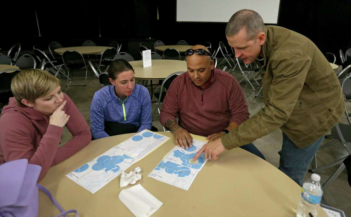 Emily Miller (from left), Marissa Mueller, Rex Brien, all of SAMMinistries, and Justin Schmitt, of USAA, look at a map during the South Alamo Regional Alliance for the Homeless annual point-in-time count held Thursday Jan. 26, 2017.