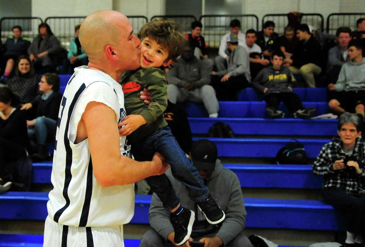 Bridgeport police officer Pedro Rosa Jr. kisses his son Pedro Rosa III, 2, after his department played against the Fairfield Police Department in the Barnum Festival Bridgeport and Fairfield Police Department and Fire Department Basketball Tournament at the Cardinal Shehan Center in Bridgeport, Conn., on Thursday Jan. 26, 2017. Proceeds from the tournament will support the 2017 Barnum Festival.