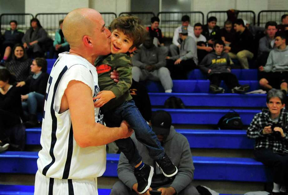 Bridgeport police officer Pedro Rosa Jr. kisses his son Pedro Rosa III, 2, after his department played against the Fairfield Police Department in the Barnum Festival Bridgeport and Fairfield Police Department and Fire Department Basketball Tournament at the Cardinal Shehan Center in Bridgeport, Conn., on Thursday Jan. 26, 2017. Proceeds from the tournament will support the 2017 Barnum Festival. Photo: Christian Abraham / Hearst Connecticut Media / Connecticut Post