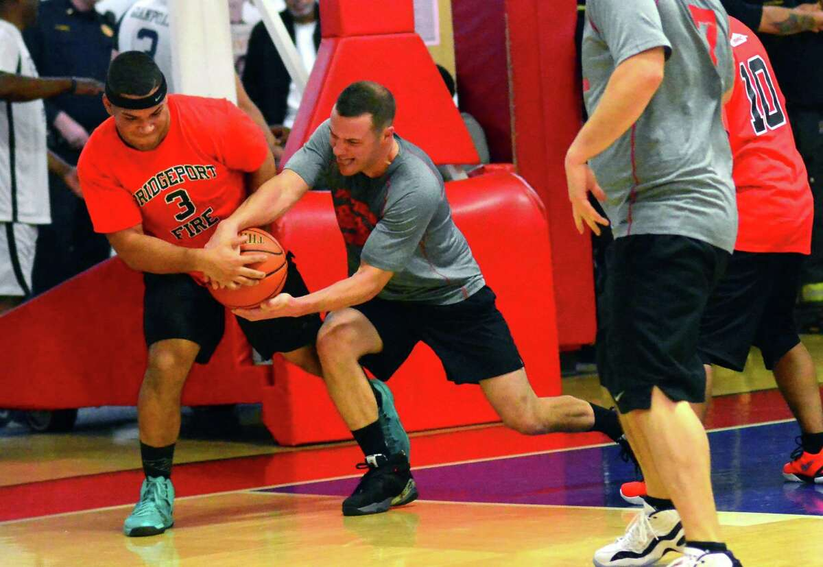 Bridgeport Fire Department's Jaime Rodriguez, left, and Fairfield Fire Department's Matt Striebe struggle for control of a rebound during the Barnum Festival Bridgeport and Fairfield Police Department and Fire Department Basketball Tournament at the Cardinal Shehan Center in Bridgeport, Conn., on Thursday Jan. 26, 2017. Proceeds from the tournament will support the 2017 Barnum Festival.