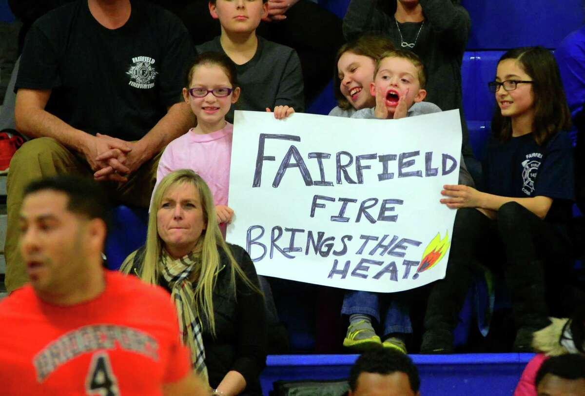Cameron Higgins, 3, cheers for the Fairfield Fire Department team as it plays against the Bridgeport Fire Department in the Barnum Festival Bridgeport and Fairfield Police Department and Fire Department Basketball Tournament at the Cardinal Shehan Center in Bridgeport, Conn., on Thursday Jan. 26, 2017. Also with Cameron from left to right is Courtney Higgins, 7, Sydney Rainis, 12, and Kyleigh Higgins, 9. Proceeds from the tournament will support the 2017 Barnum Festival.